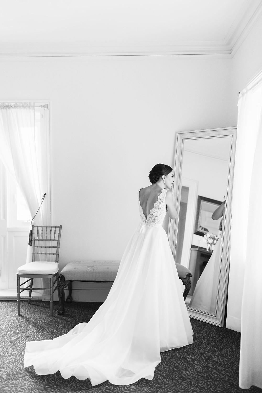 bride putting on earrings looking in full body mirror