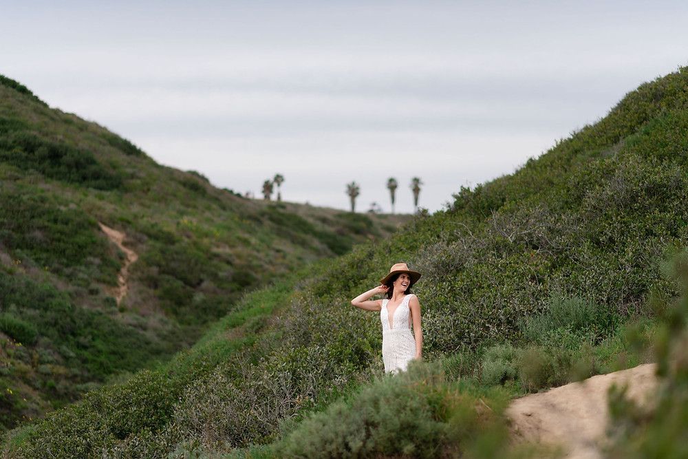 bride posing on a green hillside with palm trees in the background and a stylish hat