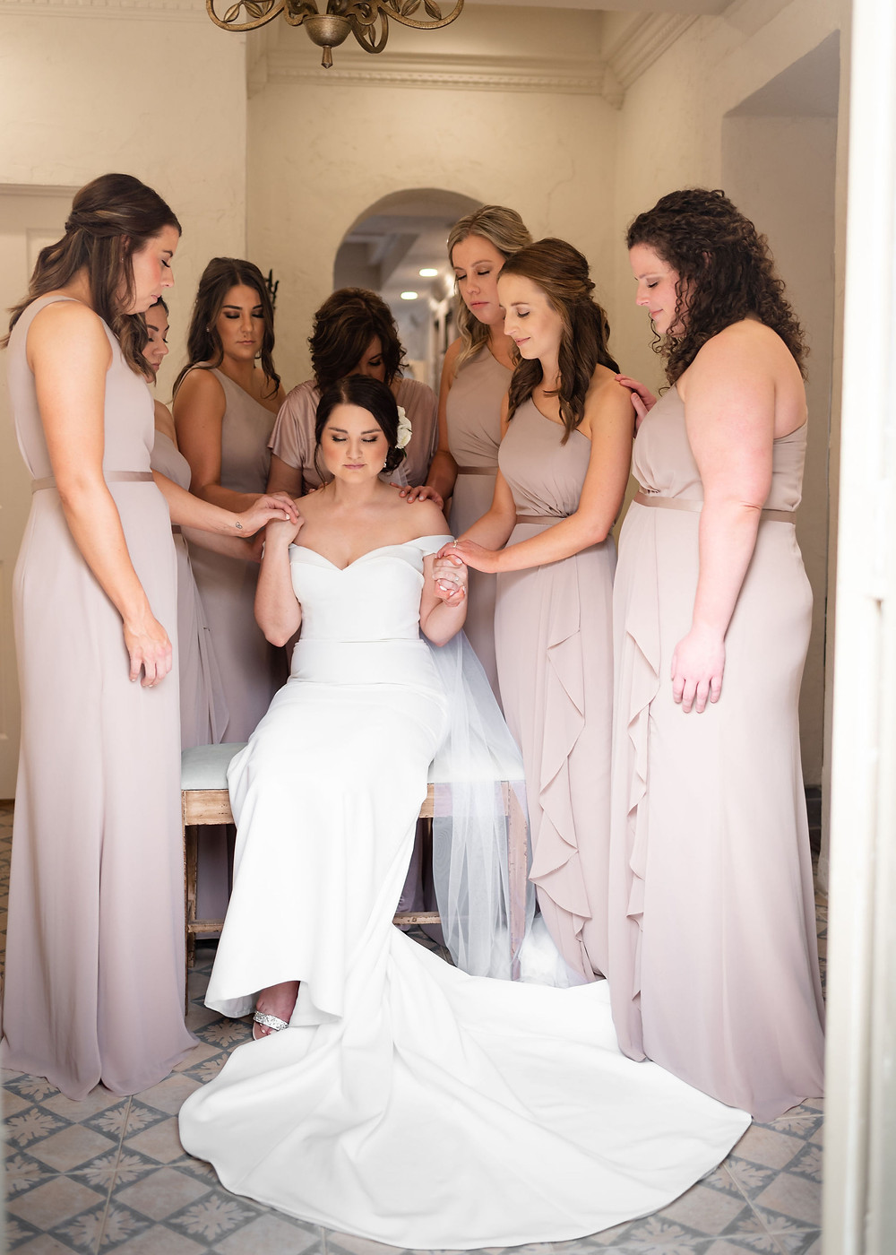 bridesmaids praying over bride before wedding at villa antonia