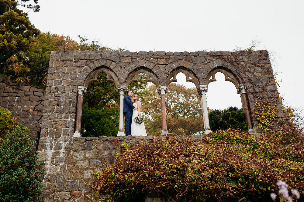 bride and groom stand on arches at hammond castle museum