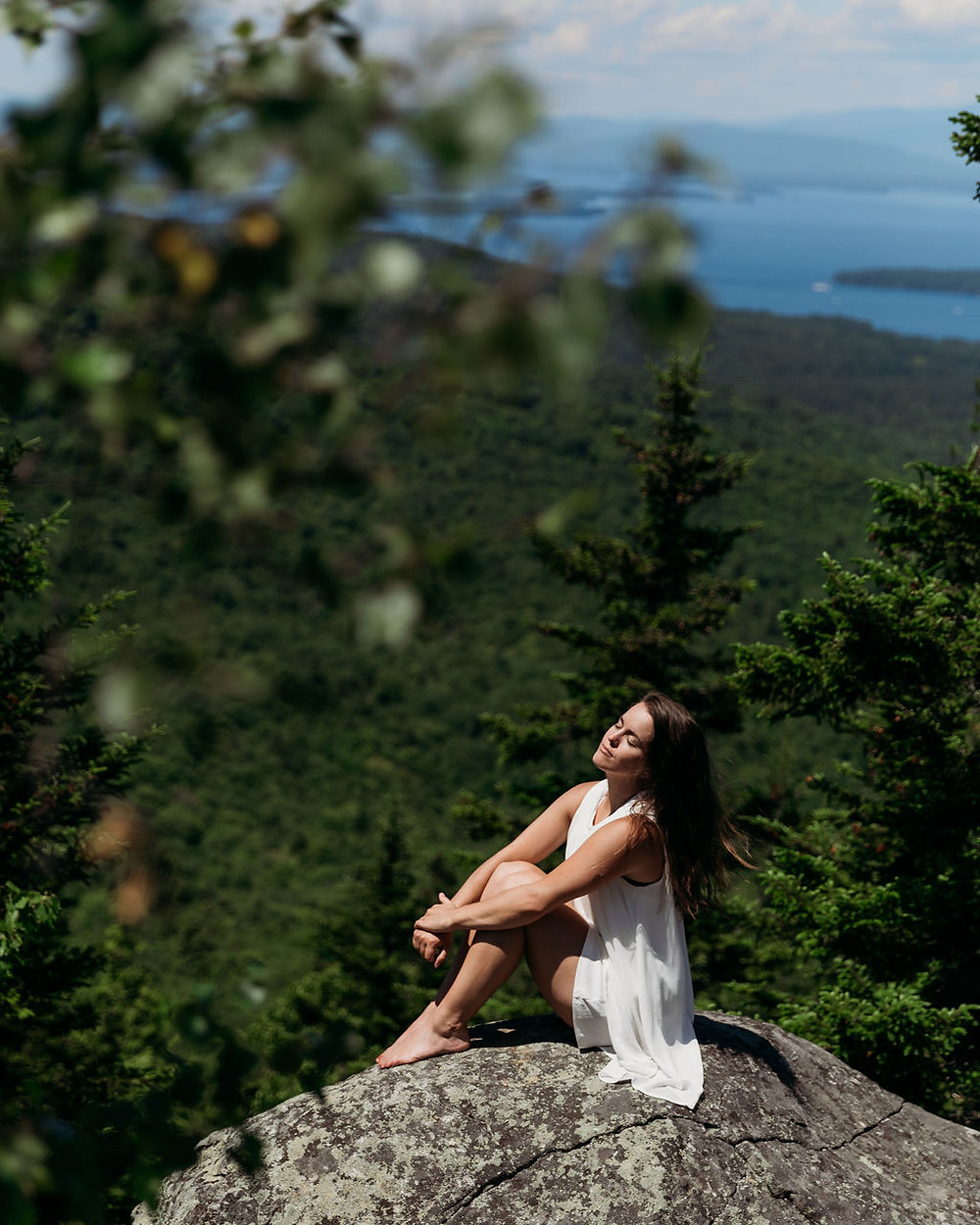 girl sitting on rock on summit of mt major with lake winnipesaukee in the background