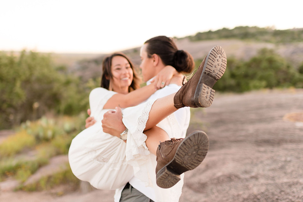 groom holds bride in his arms like a baby. the focus of the photo is on the bride's hiking boots to enhance the adventure elopement vibe