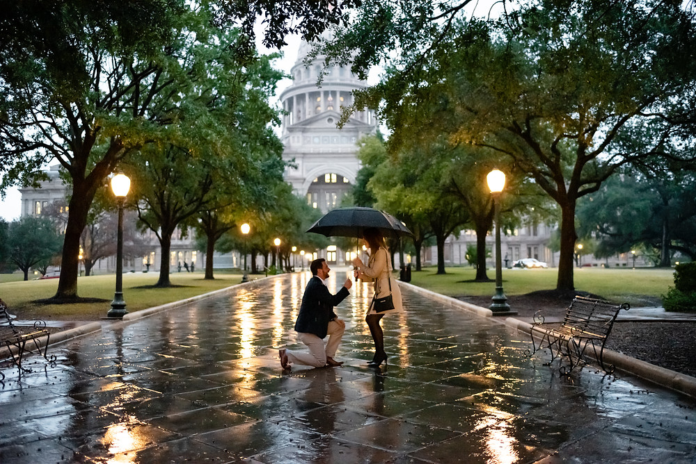 guy down on one knee proposing in the rain in front of Austin Capitol building