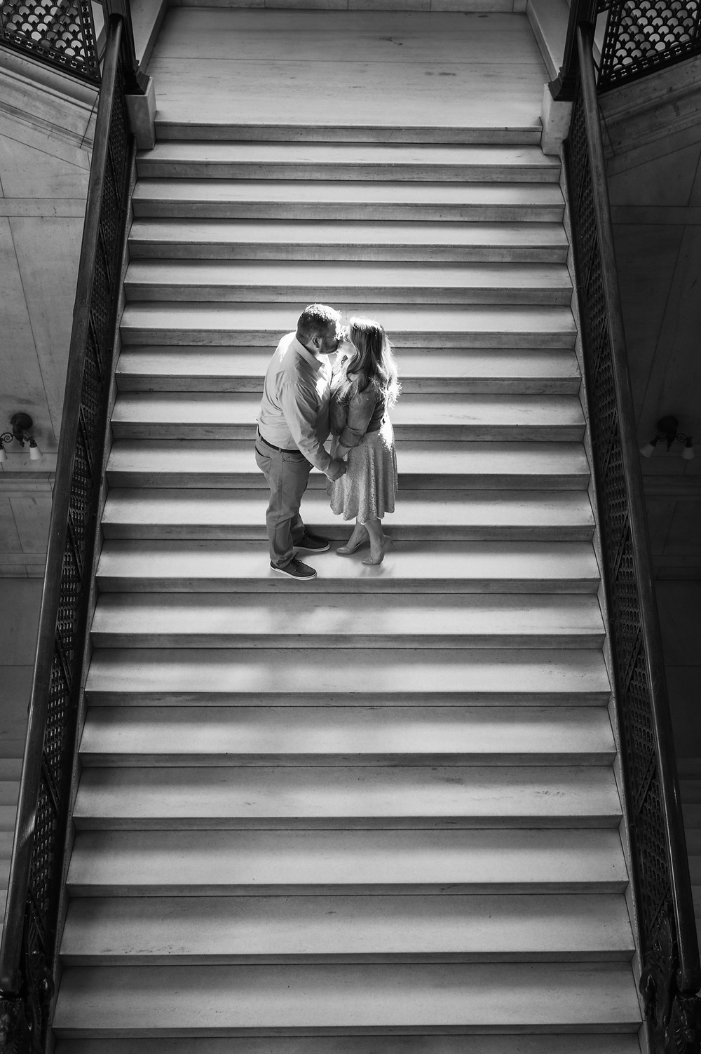 birds eye view of couple on staircase with dramatic shadows
