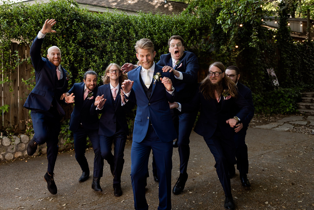 groomsmen running to jump on groom
