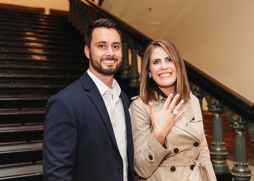 newly engaged couple showing engagement ring to the camera