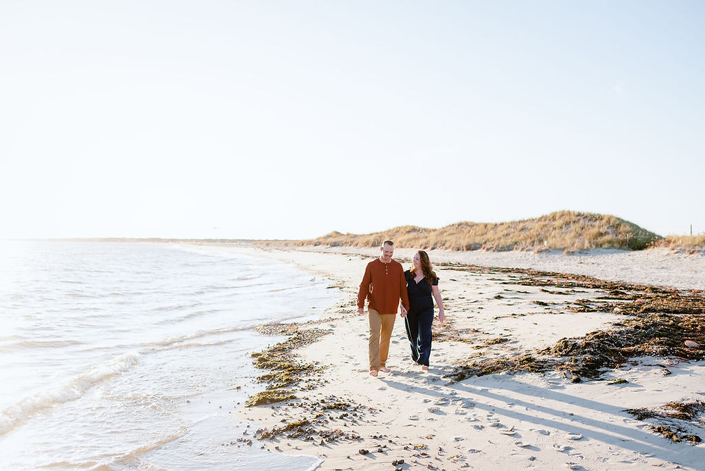 couple holding hands walking on beach at lighthouse inn in West Dennis Cape cod, MA