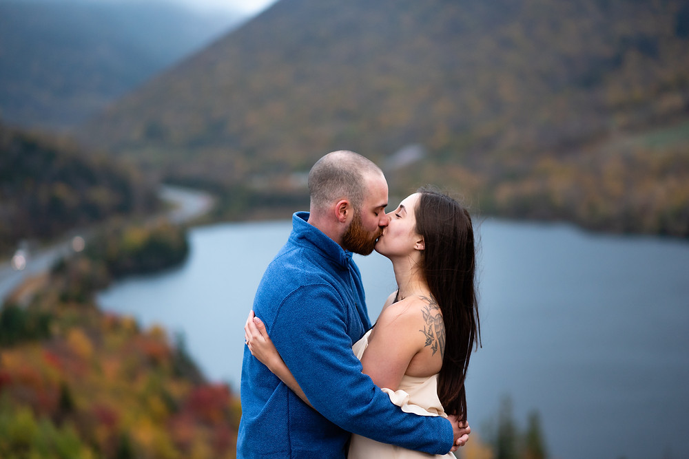 couple kissing with echo lake in the background in the white mountains of new hampshire