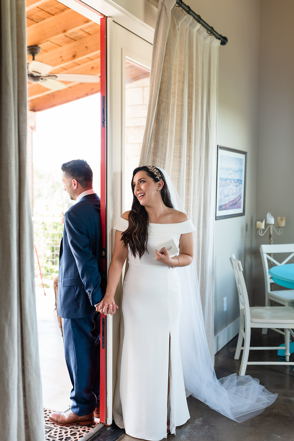 bride and groom stand on each side of a closed door holding hands for their no look first look before their wedding