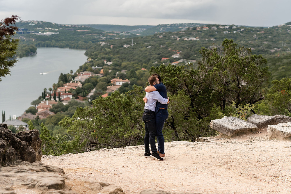 the couple hugs after proposal with view from mount bonnell in distance