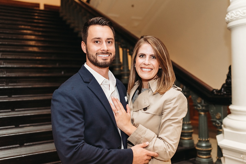 newly engaged couple smiling and posing for camera in Austin Capitol building