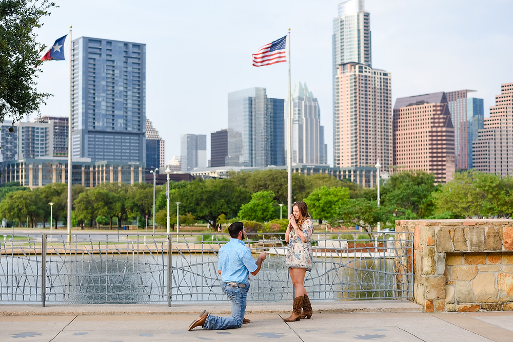 man down on one knee proposing by the Palmer Events Center in austin with the austin skyline in the background