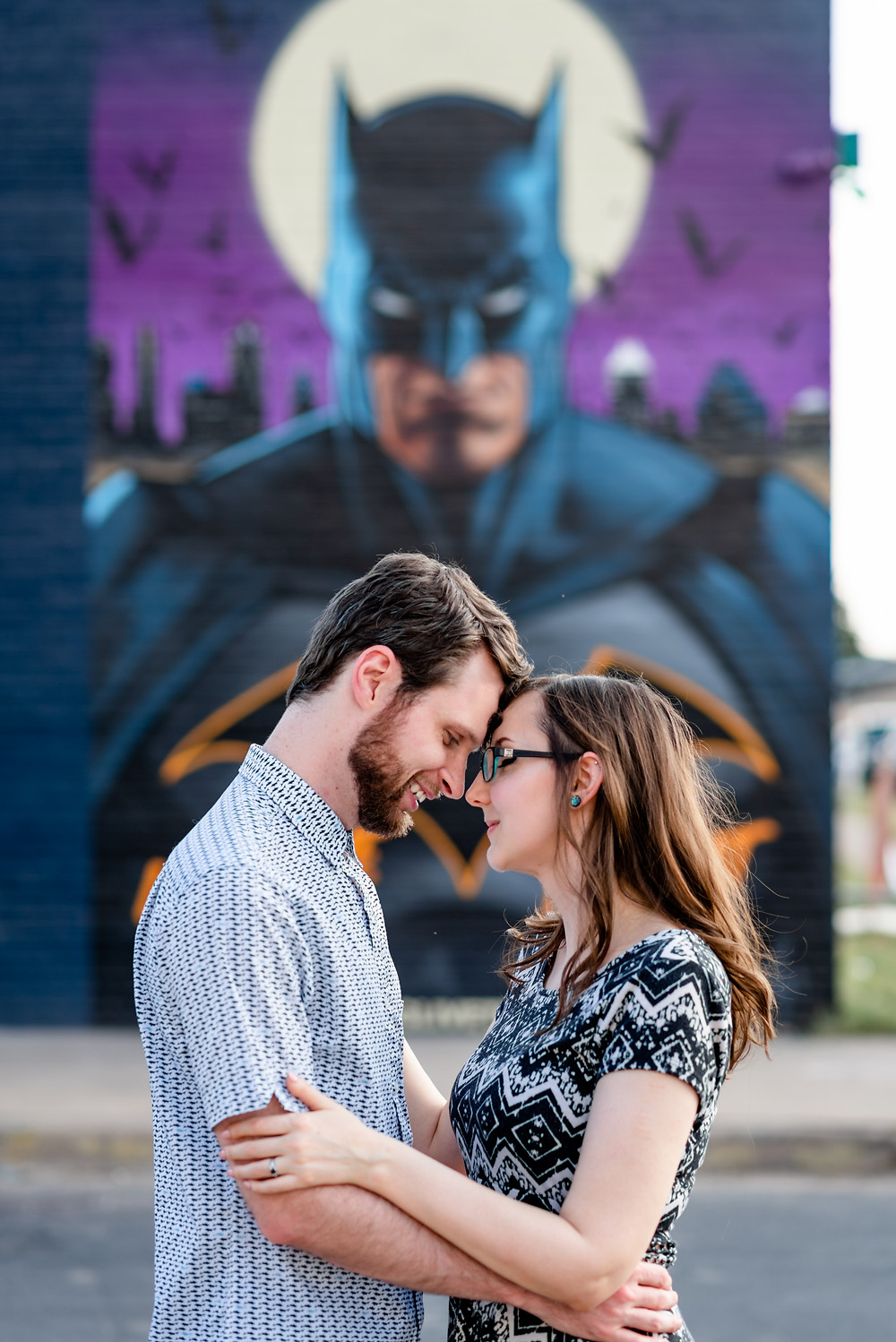girl and guy stand in front of batman mural in austin for their engagement photos. They're standing face to face, with their foreheads touching and their arms wrapped around each other.