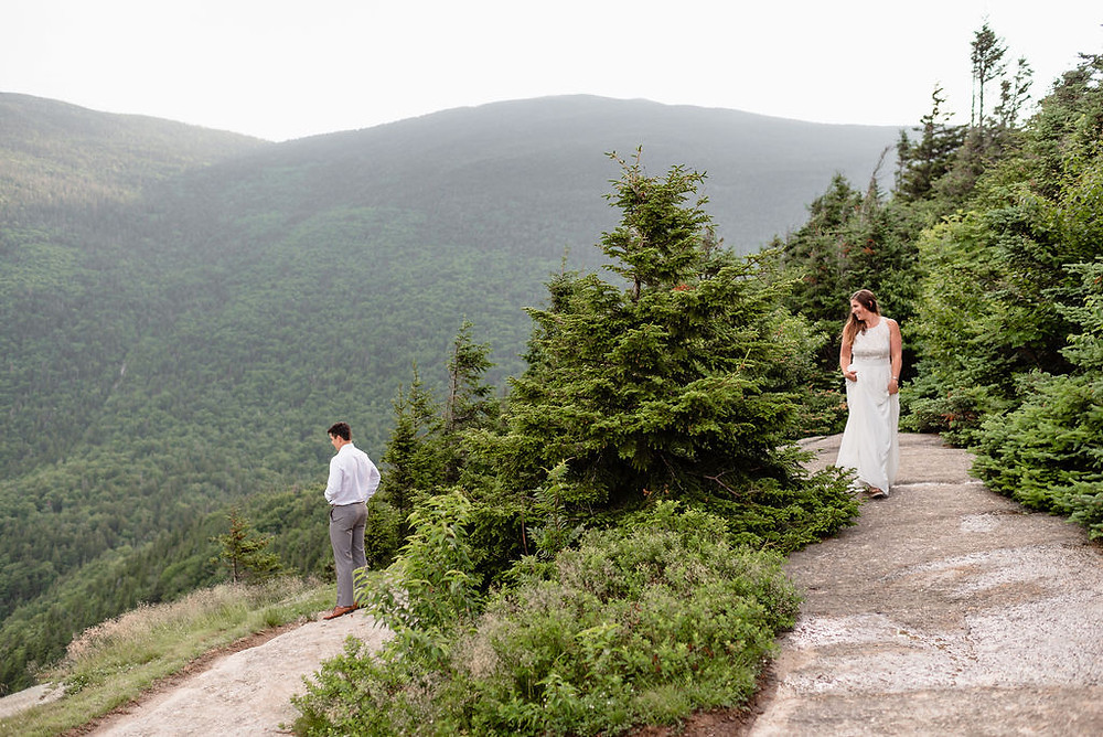 wide angle view of the elopement first look. the bride is walking towards the camera along a dirt parh with the groom in the distance