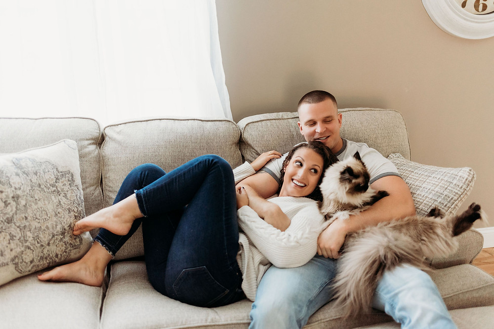 in home engagement session with couple posed on couch with cat