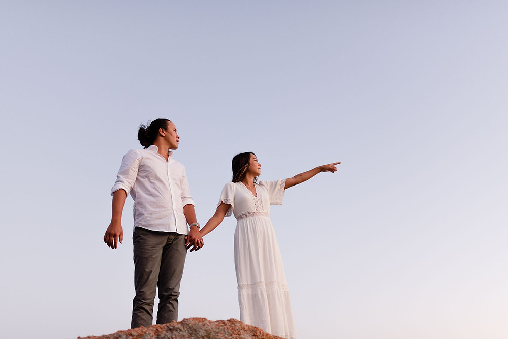 couple standing next to each other holding hands. the girl is pointing off into the distance at something they're both looking at. the point of view of the camera is from below so you can only see the couple and the sky