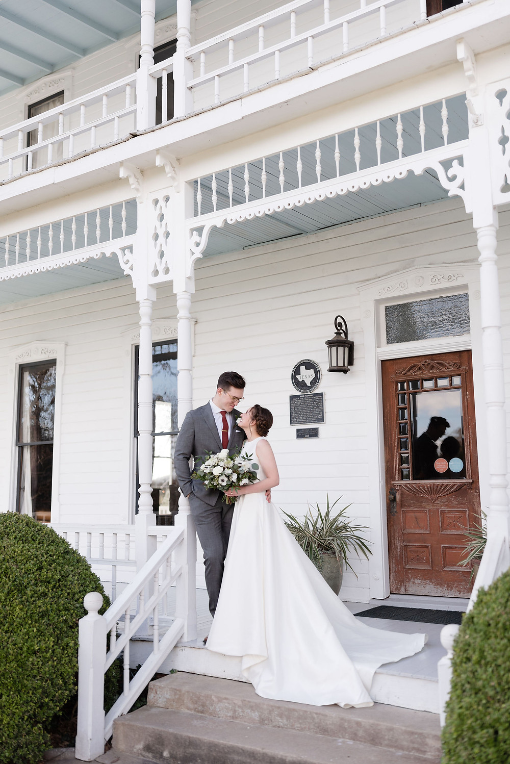 a couple posing for their wedding photos on the porch at Barr Mansion