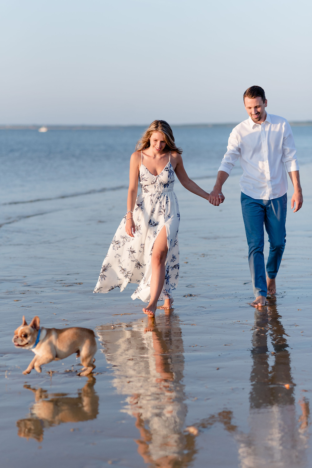 couple walking along the beach holding hands with their dog running ahead of them