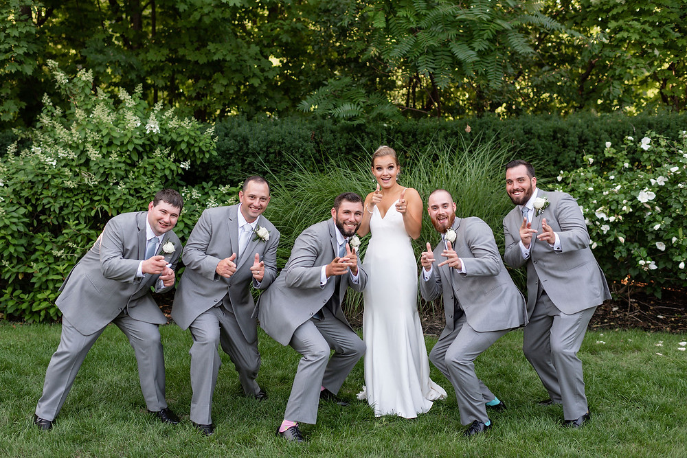 bride and groomsmen doing finger guns at the camera