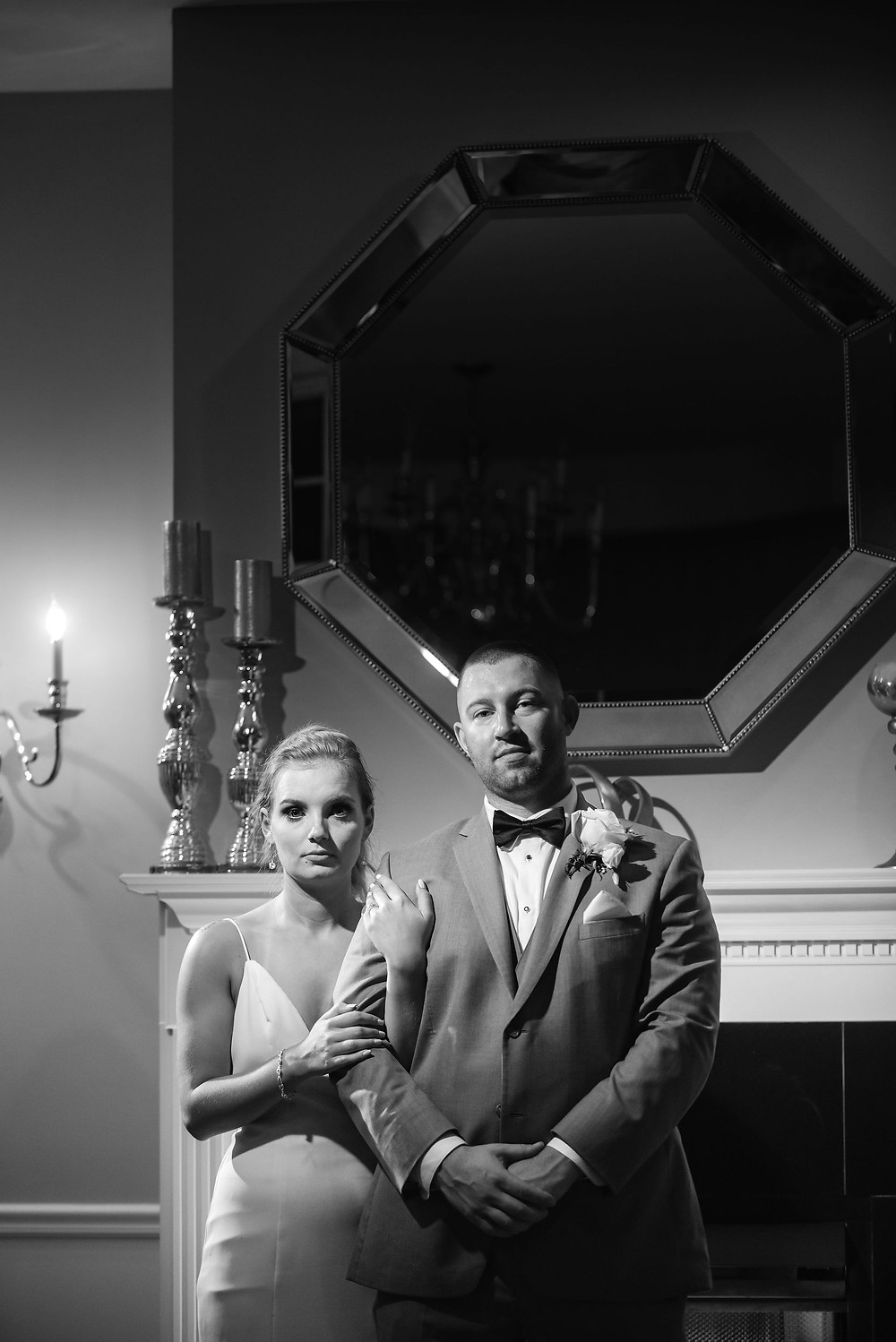 black and white moody photo of bride and groom in front of fireplace in the ballroom at chocksett inn