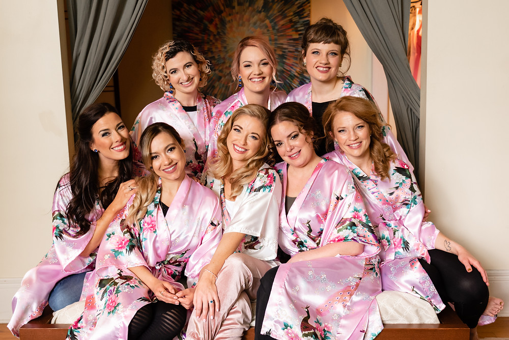 bridesmaids sitting on bed in robes