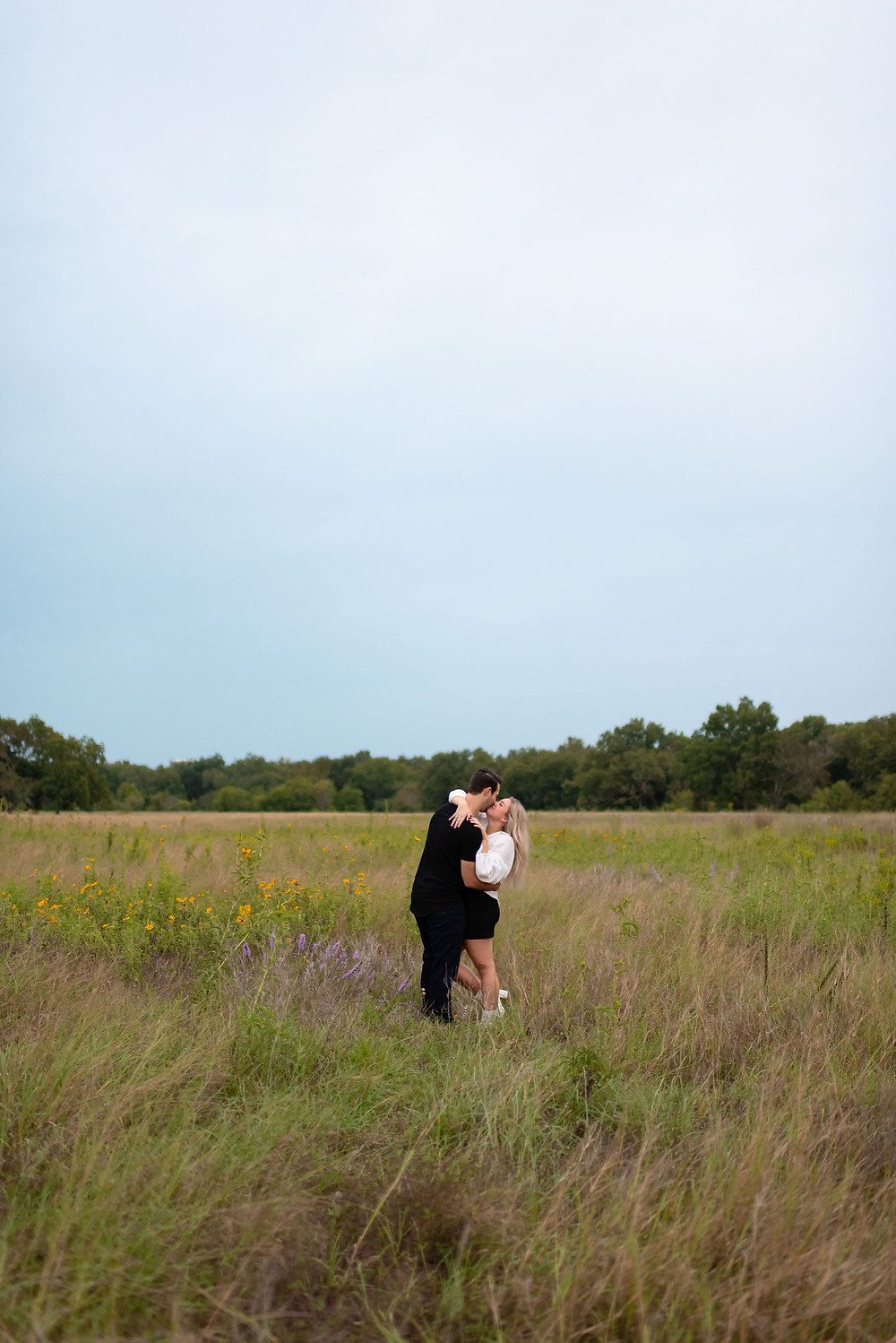 wide angle shot of couple standing in field at berry springs park in georgetown, texas for engagement photos