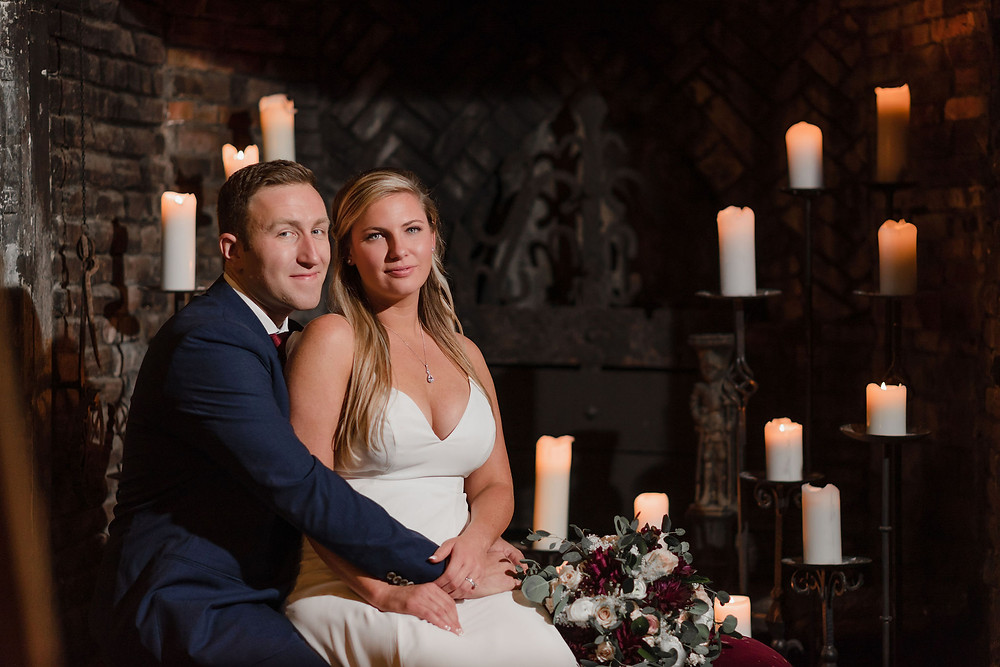 bride and groom sitting in front of large fire place with lit candles