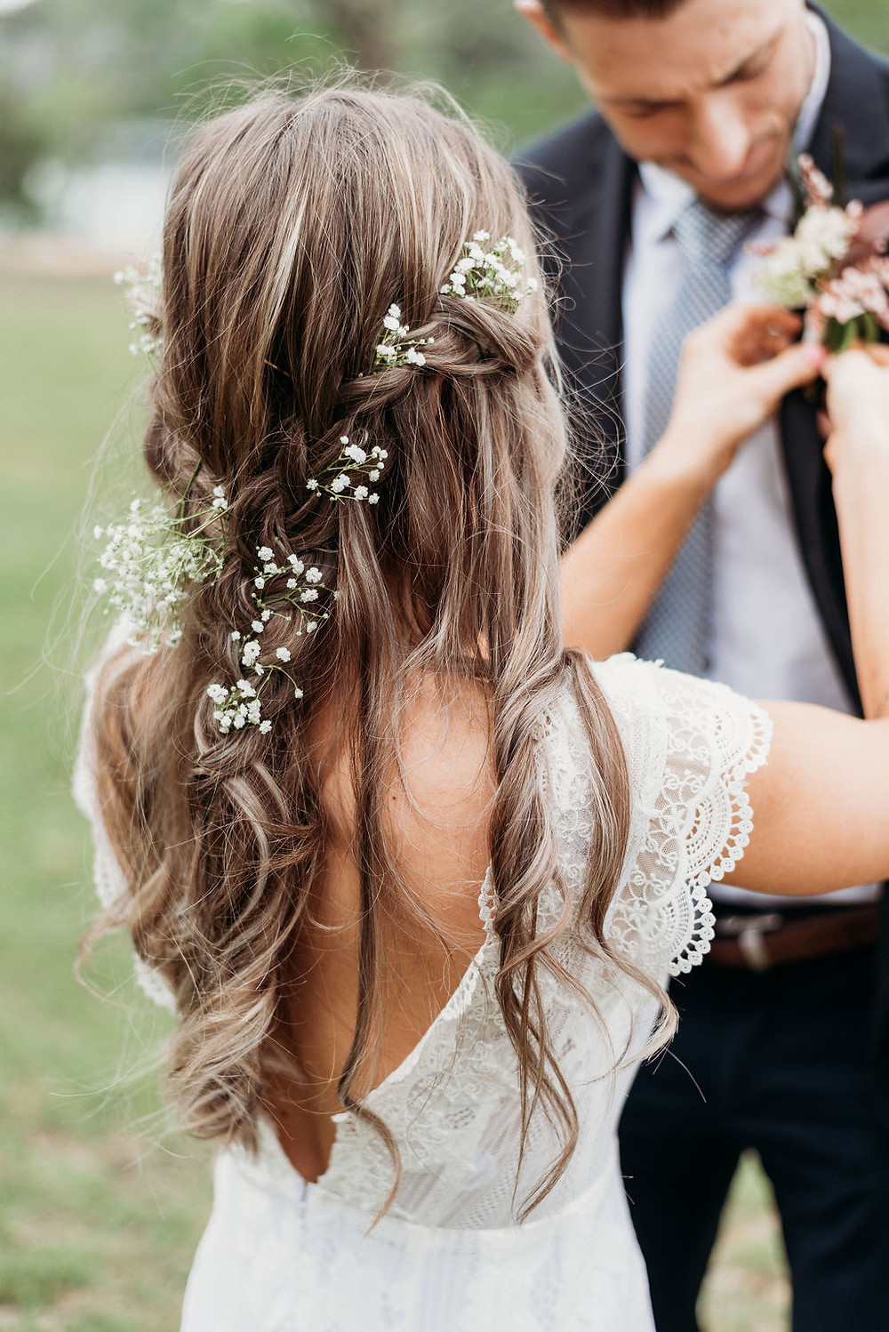 bride pins boutonnière on groom's lapel. You can see the back of the bride's to see her boho hair style with baby's breath in her hair for her austin elopement.