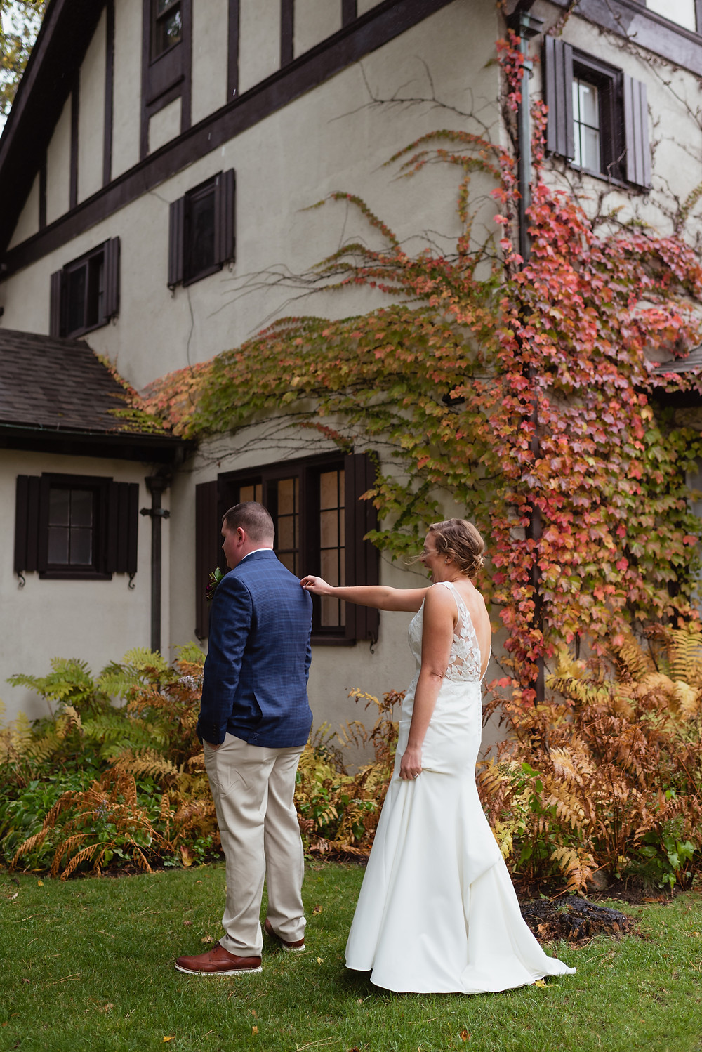 bride tapping groom on shoulder during first look outside Ivy Manor Inn in Bar Harbor, ME