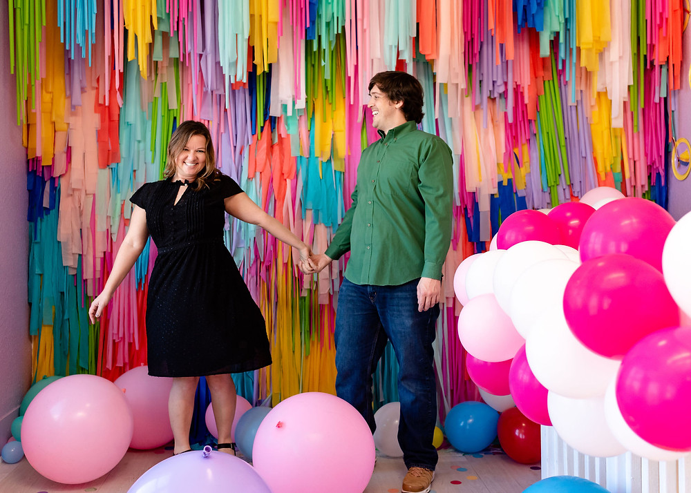 couple at the fomo factory in austin with balloons and a ribbon wall