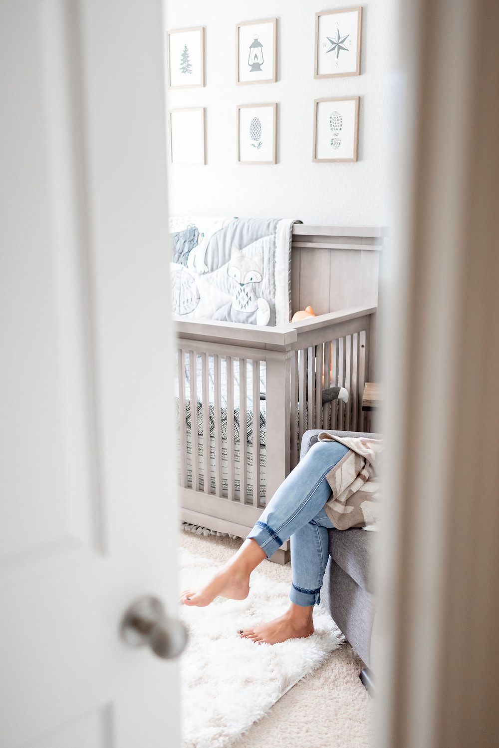 in home newborn session through the door photo with only the mom's legs showing as she is breast feeding