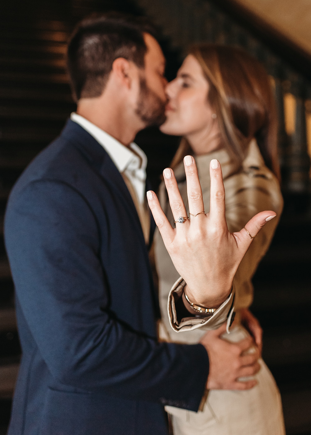 newly engaged couple showing the engagement ring to the camera while kissing