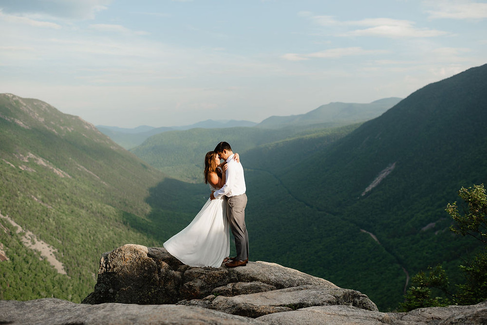 epic mountain elopement photo.. mount willard elopement . bride and groom kissing on a mountain summit in new hampshire