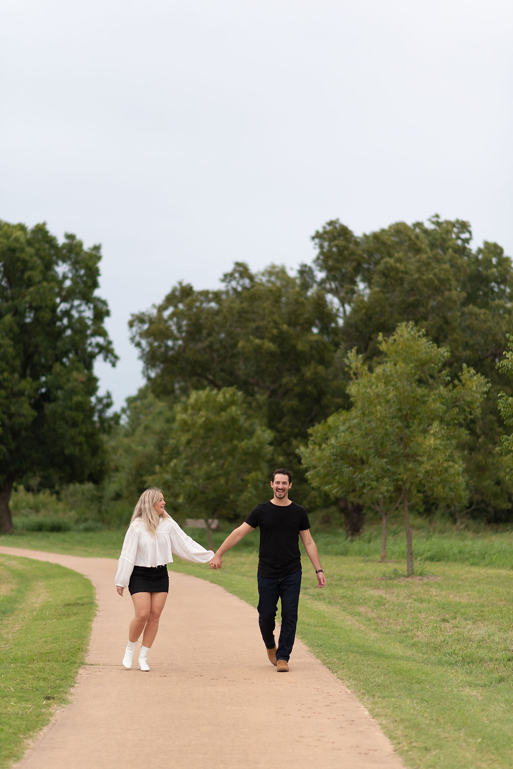 couple walks hand in hand towards the camera, smiling at each other during engagement photos