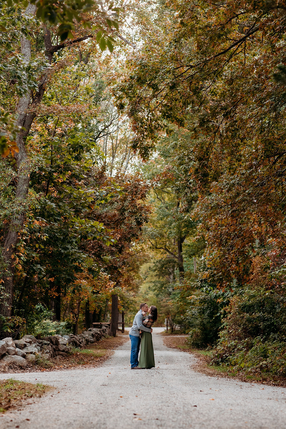 guy and girl stand chest to chest kissing in the middle of the street. the couple is small in the frame as they are far away . trees line the road with fall foliage