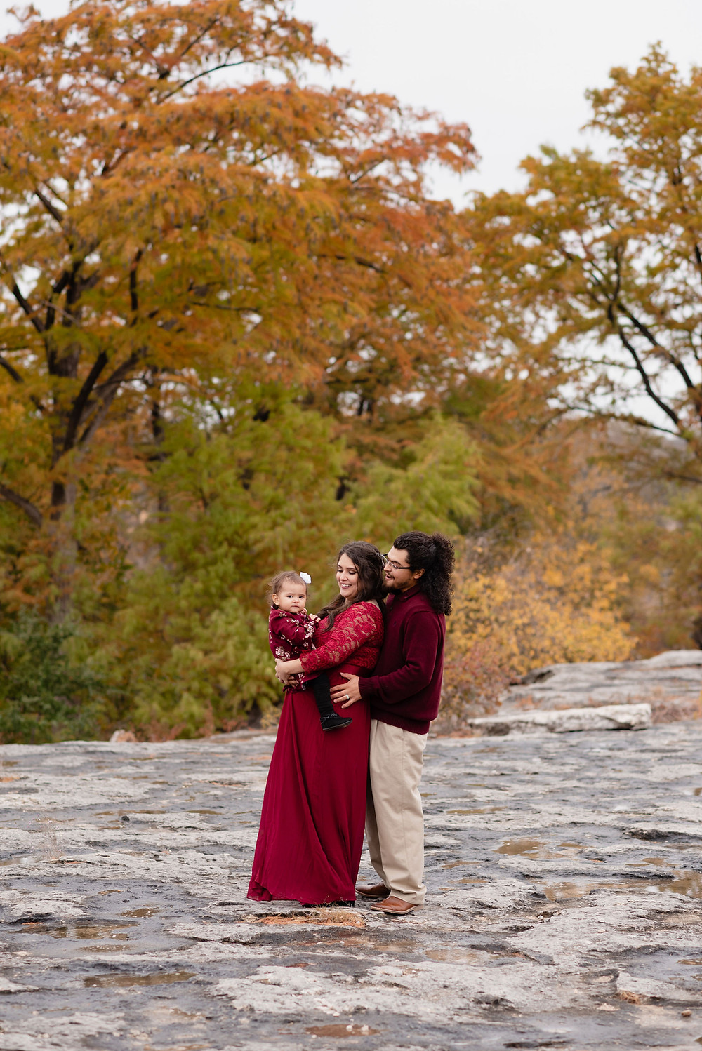 family standing on rocks at McKinney Falls State park during the fall