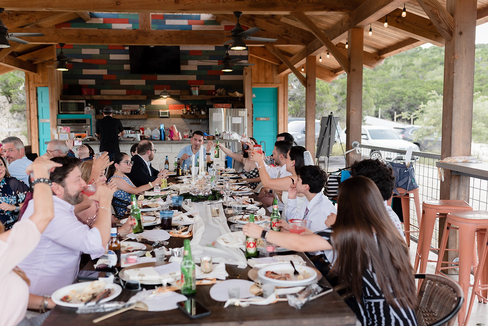 Hill Country Casitas reception pavilion. guests are seated along one long table and everyone has their glasses raised in the air after a speech