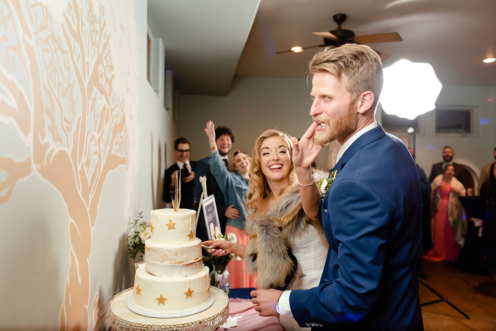 bride smashing cake into groom's face during cake cutting