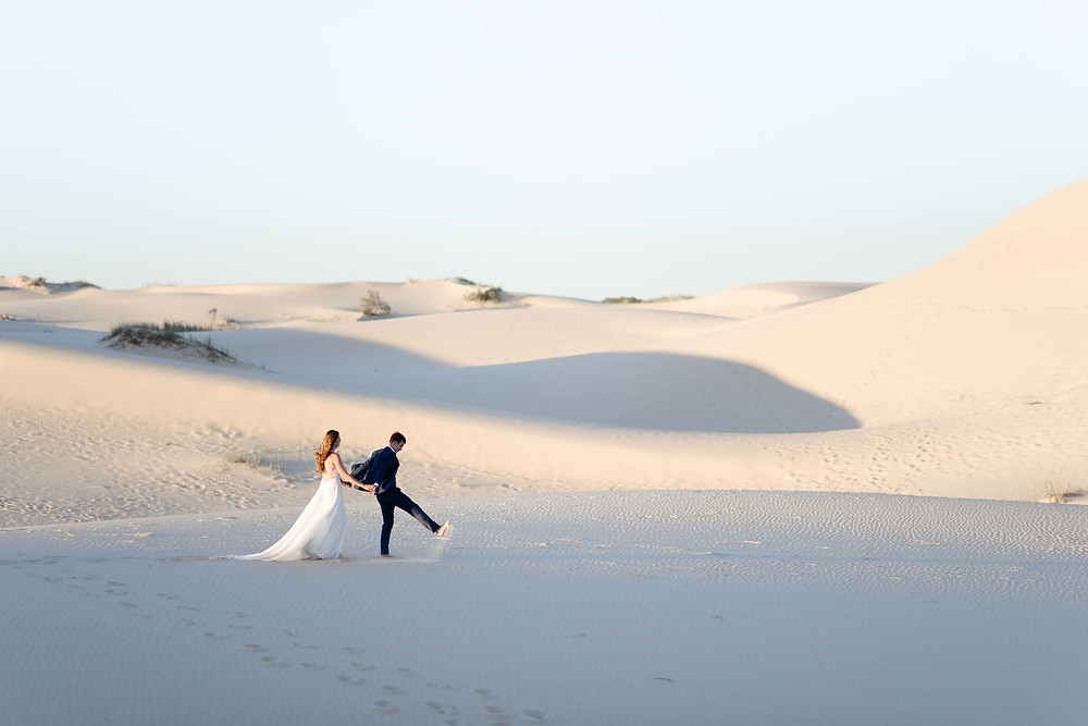 groom leads bride along the edge of a hill, kicking sand as he walks