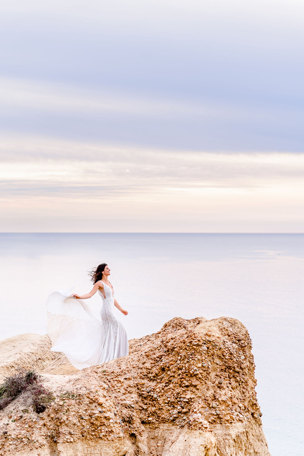 bride holding up train of dress on a cliffside in california with a purple sunset in background