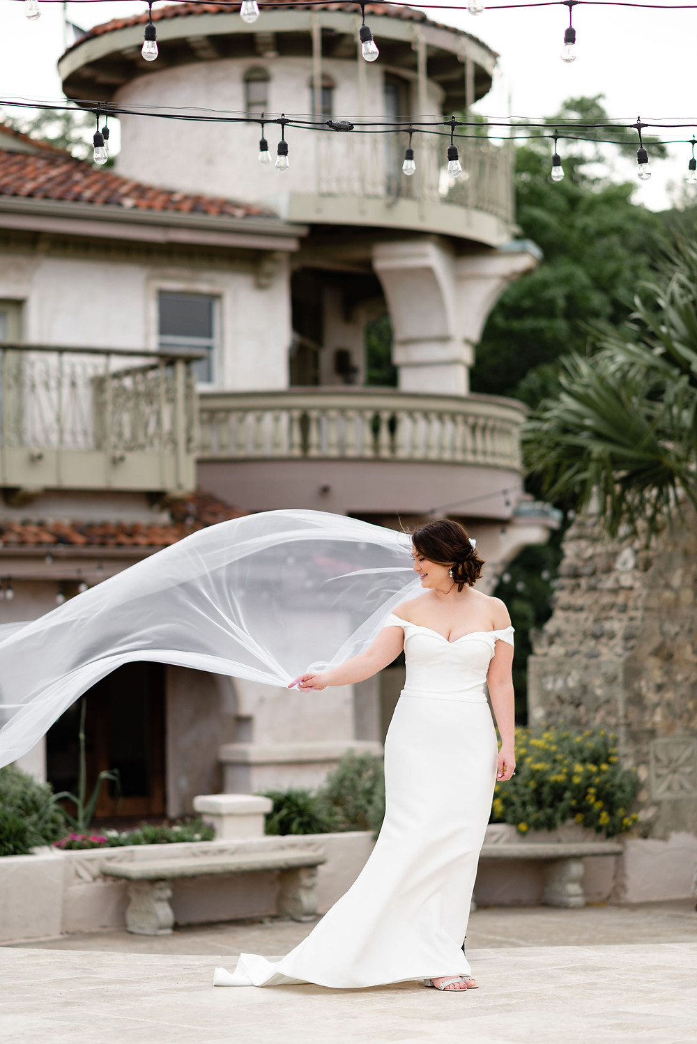 bridal portrait in the courtyard entry of villa antonia with venue in background. wind is blowing the veil and the bride is holding on to it laughing