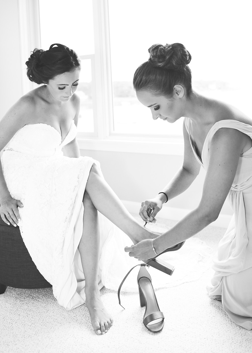 bridesmaid putting on bride's shoes