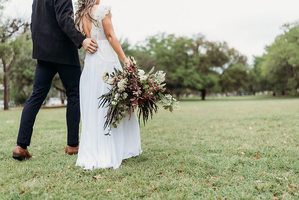 bride and groom hold hands and are walking away from the camera. bride hangs her bridal bouquet down to her side. They are small in the frame and you can see the field behind them. Austin elopement at festival beach next to lady bird lake. you cannot see their faces. the top of the photo cuts off at their shoulders.