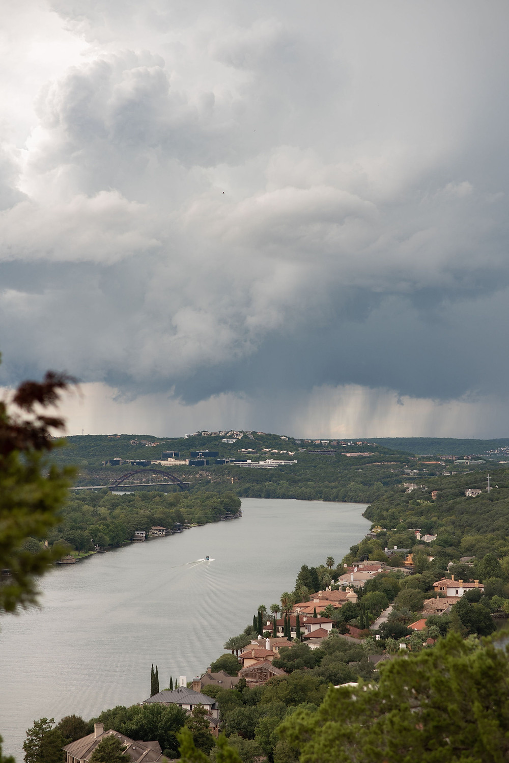 storm clouds and rain in the distance over lake travis. you can see the penny backer bridge in the distance. view from mount bonnell