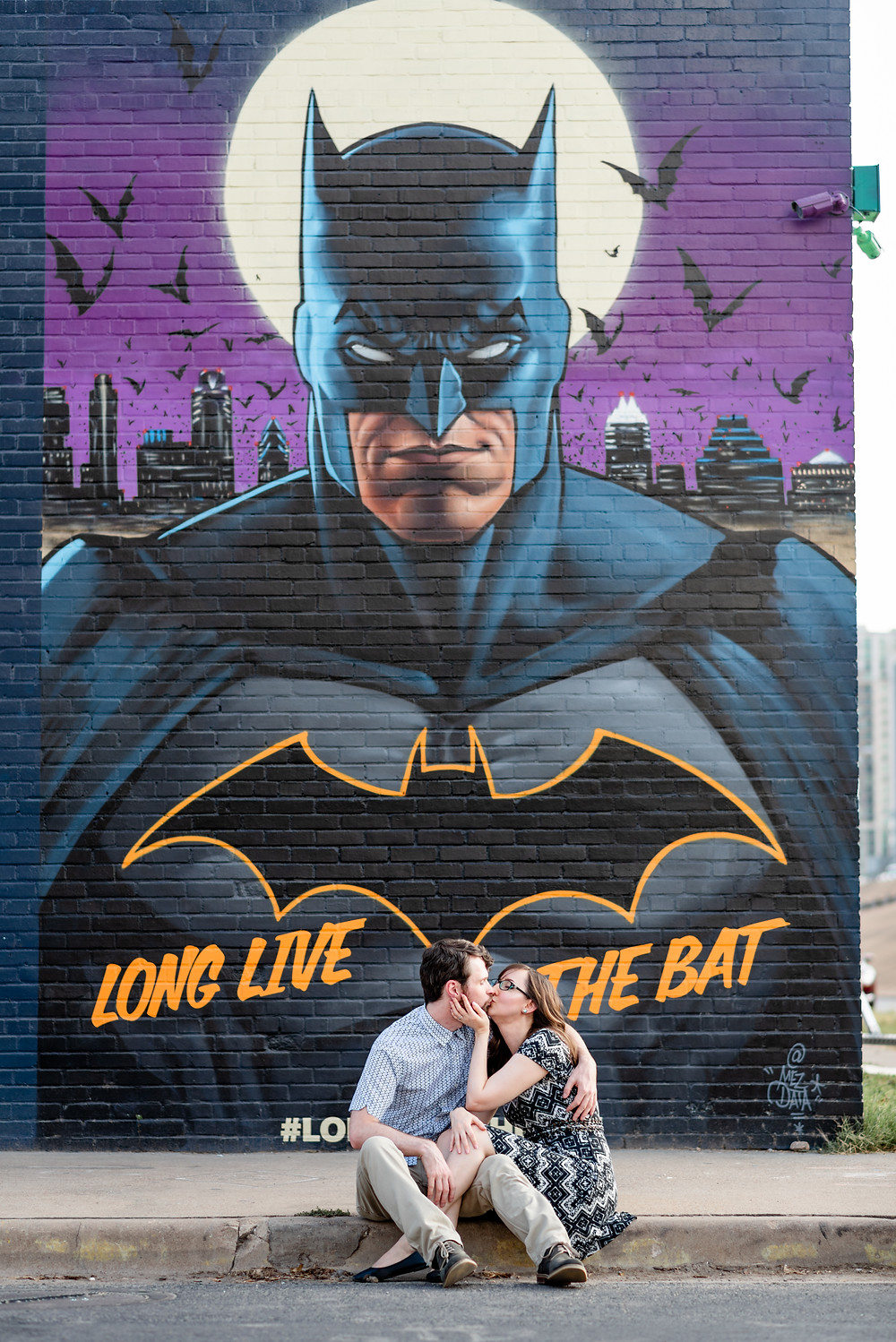 girl and guy stand in front of batman mural in austin for their engagement photos. They are sitting side by side on the ground, kissing. The girl has her hand on the guy's jawline to bring him in closer