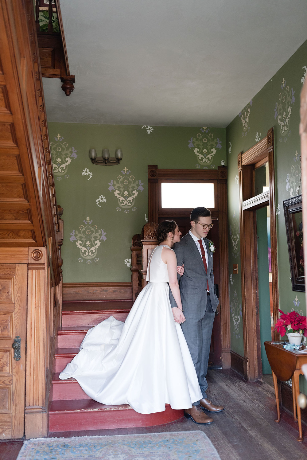 a couple praying together before their wedding. they are standing on the stairs at Barr Mansion