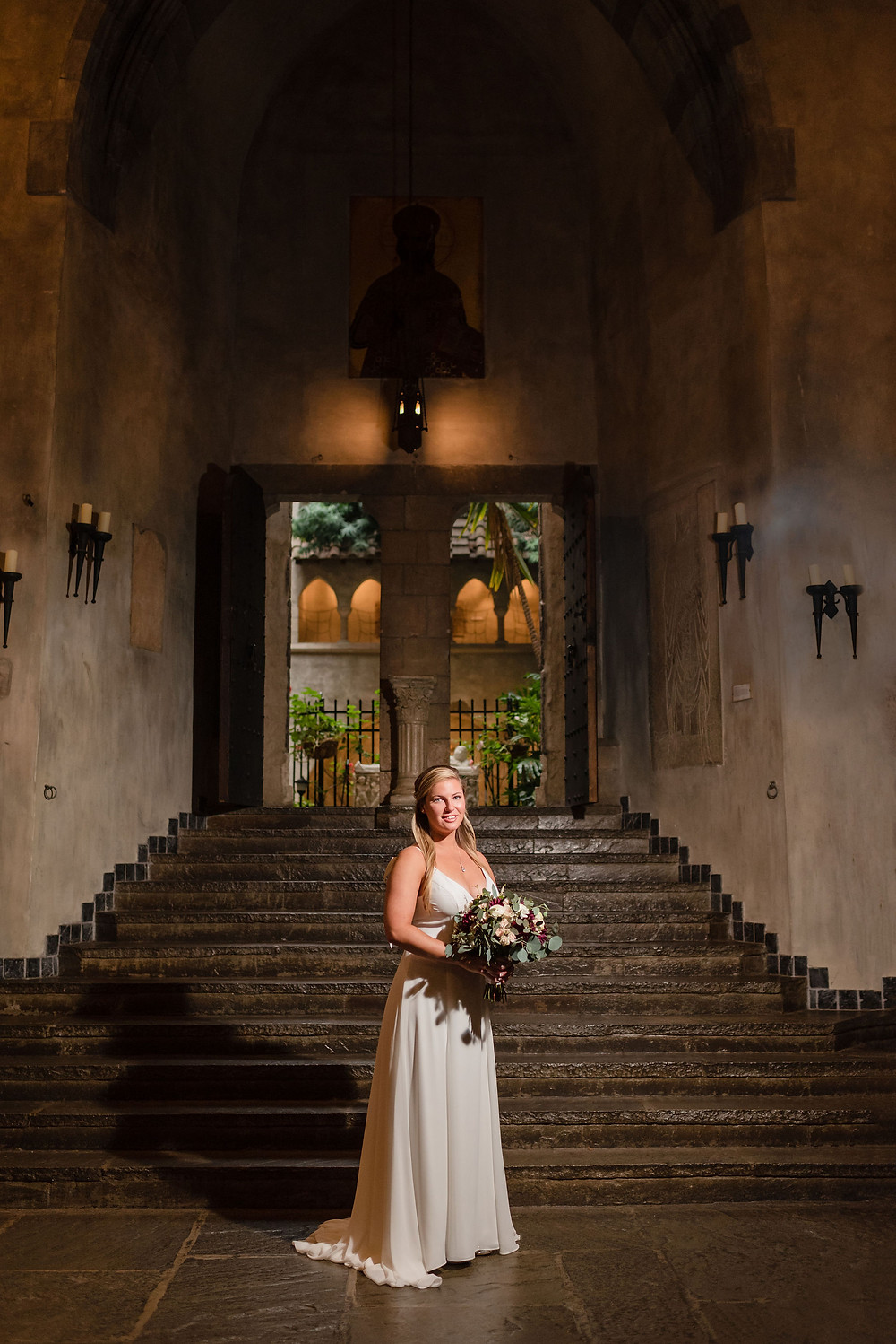 bride posing in front of stairs in the great hall. through the doors behind her is where the courtyard is