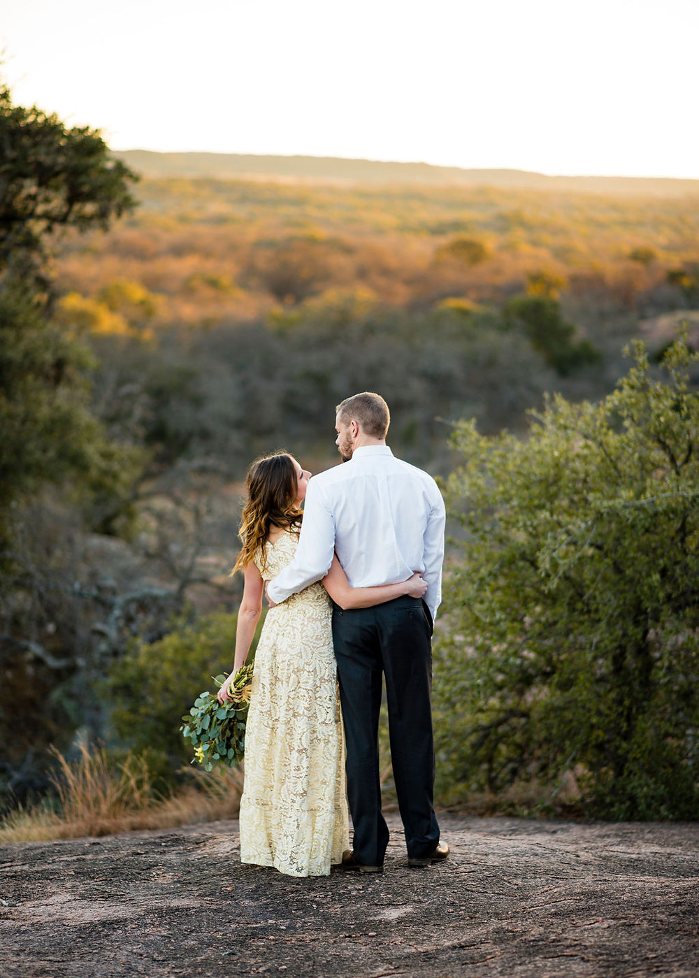 bride and groom look out at the view of the texas hill country from enchanted rock. fall elopement photo during golden hour
