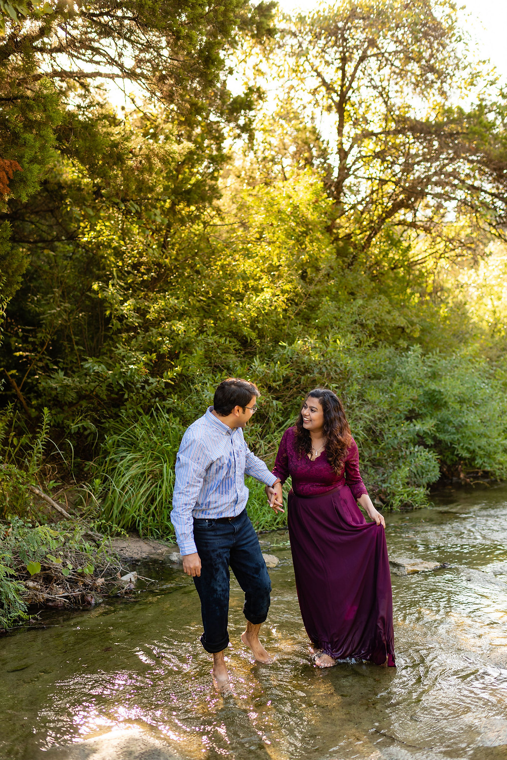 girl and guy smile at each other while walking through water at bull creek in austin which is part of the greenbelt