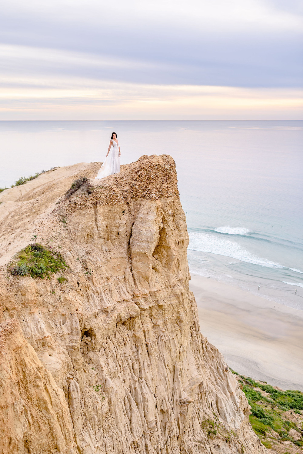 bride standing on cliffside at ho chi minh trail in san diego